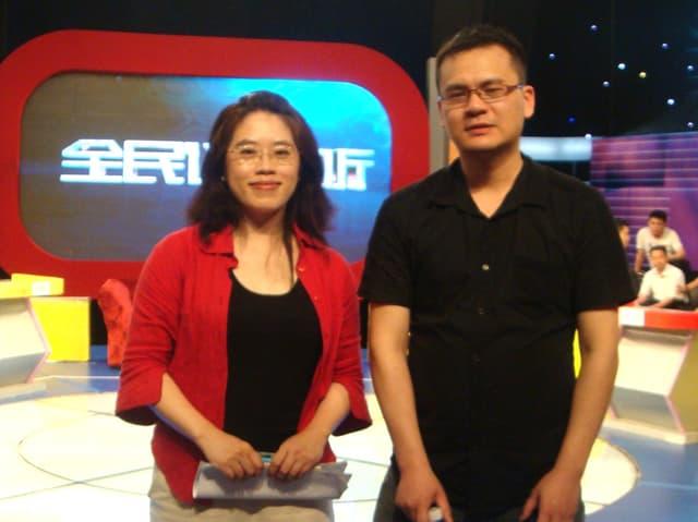 Eine Frau und ein Mann stehen in einem TV-Studio, hinter ihnen ist eine grosser rotgerahmter Bildschirm.