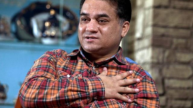 Ilham Tohti in kariertem Hemd. Die rechte Hand hat er auf seine Brust gelegt.