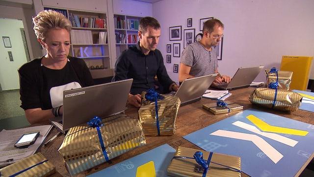 Zwei Männer und eine Frau sitzen je an einem Laptop, darum herum liegen Geschenke.