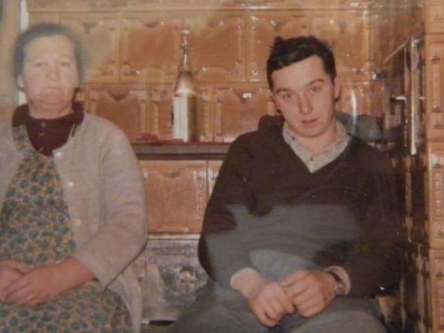 Mutter und Sohn sitzen auf der Ofenbank eines Bauernhauses.