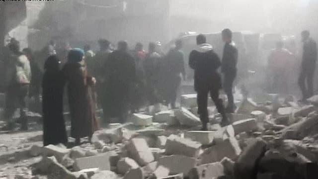 Mensch im Staub einer bombardierten Strasse in Aleppo.