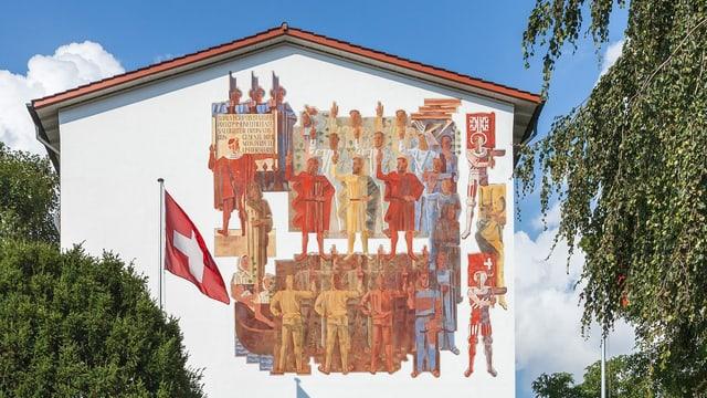 Eine bunt bemalte Fassade eines weissen Hauses. Auf der Wandbemalung sind Wappen und Männer zu sehen, die einen Eid schwören.