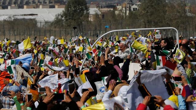 Der Papst fährt mit seinem Papamobil durch die Menge.