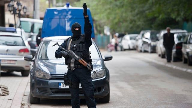 Schwer bewaffneter, schwarz gekleideter Polizist seht auf der Strasse.