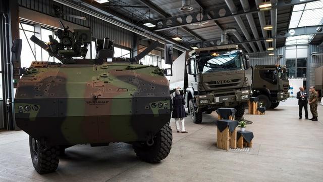 vista en ina halla, parcà è in tanc ed en il fund dus camiuns militars