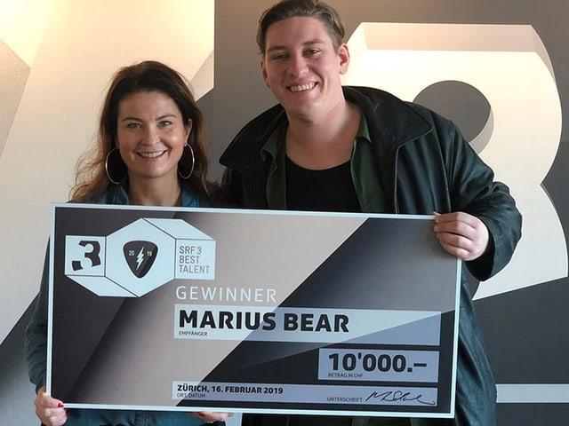Judith Wernli und Marius Bear präsentieren den Sieger-Scheck.
