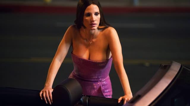 Frau mit grossem Ausschntit und Abendkleid stützt sich an Auto ab.