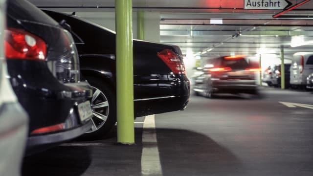 Autos in einem Parkhaus, ein Auto fährt, die anderen sind parkiert.
