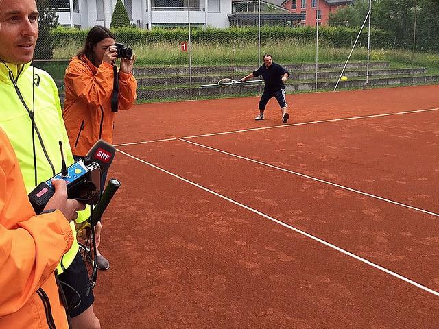 Viktor Röthlin steht mit Radioredaktoren neben dem Tennisplatz, Marco Rima spielt sich auf dem Platz ein.