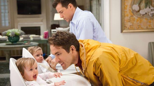 Zwei Männer kümmern sich um zwei Kleinkinder, welche in einem Kinderstuhl sitzen. Sie wirken etwas unbeholfen.