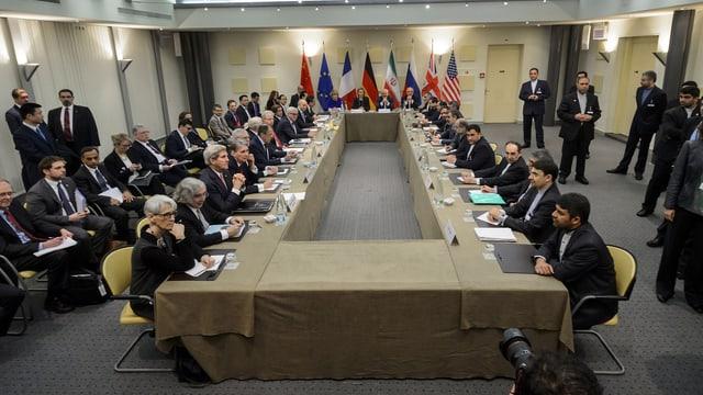 Verhandlungsteilnehmer an einem eckigen Tisch.