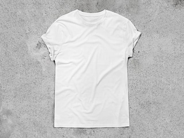 Ein weisses Shirt liegt auf einer grauen Beton-Fläche.