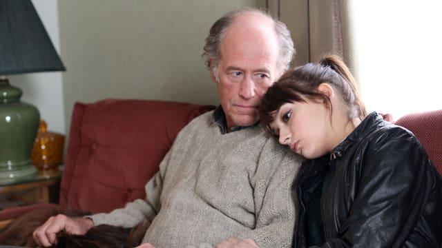 Ein älterer Mann sitzt auf dem Sofa, neben ihm eine junge Frau, die ihren Kopf an seine Schulter lehnt.
