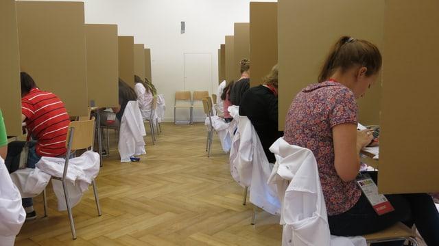 Schülerinnen und Schüler in weissen Laborkitteln bei der Arbeit.