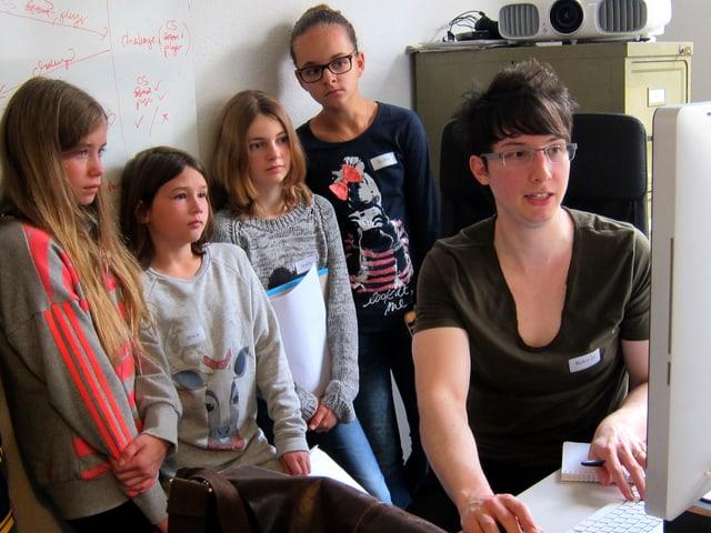 Ein Mann am Computer erklärt vier Mädchen etwas.