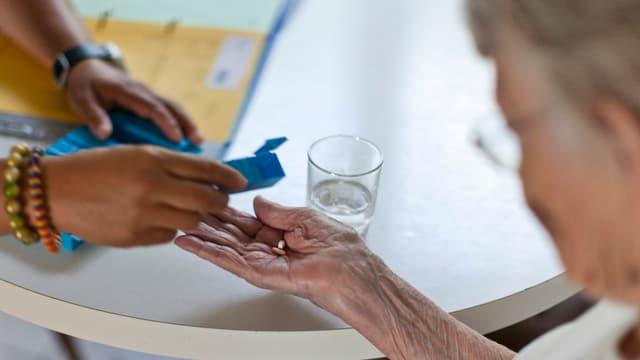 Eine Spitex-Angestellte gibt einer betagten Frau Medikamente