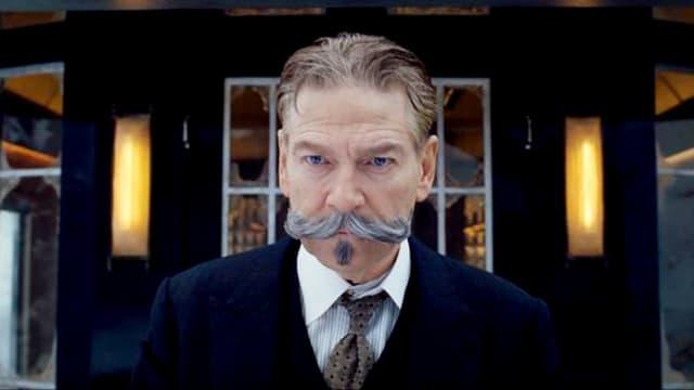 Hercule Poirot steht mit gezwirbeltem Bart vor einem erleuchteten Fenster.
