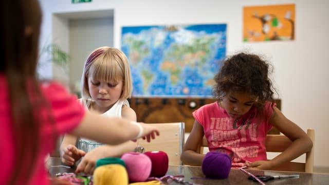 Zwei Mädchen sitzen an einem Tisch und basteln mit farbigem Garn.