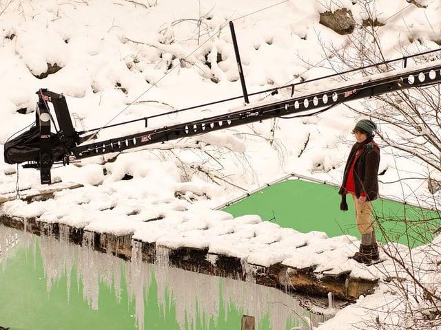 Schellenursli läuft über die verschneite Holzbrücke, darunter der Greenscreen.