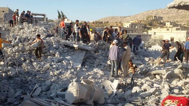 Menschen stehen auf Trümmern
