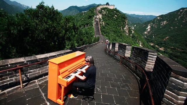 Ein Mann spielt Klavier auf der  Chinesischen Mauer.