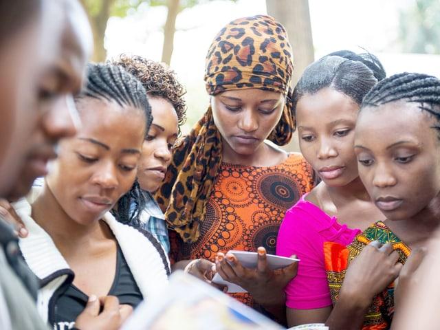 Angehende Pflegerinnen in Tansania stehen in einer Gruppe und schauen in Unterlagen.