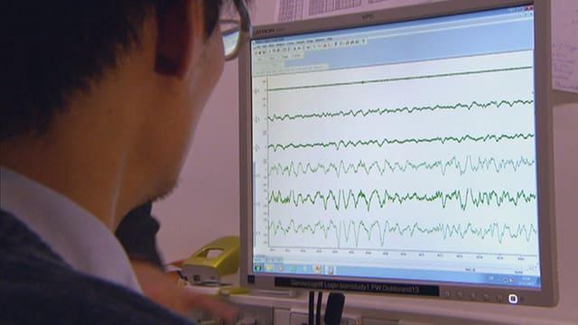 Ein Mann sitzt vor einem Bildschirm, der Hirnstromwellen zeigt.