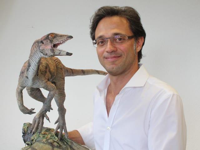 Ein Mann mit brille, davor das Modell eines Dinosauriers.
