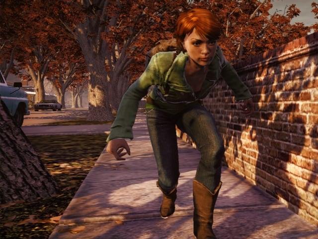 Eine Frau schleicht einer Mauer entlang.
