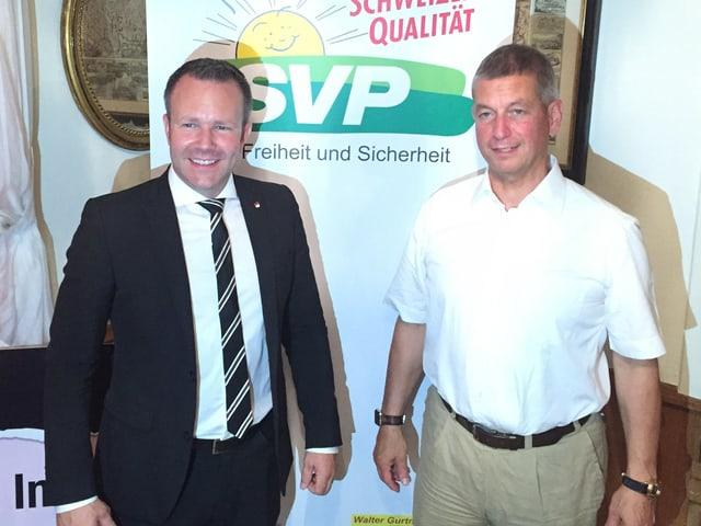 Zwei Männer vor SVP-Logo