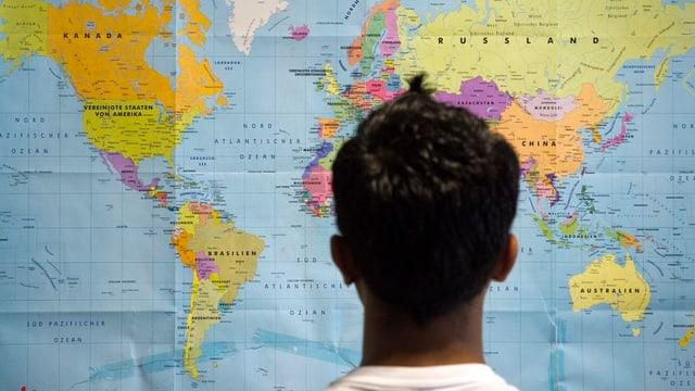 Ein dunkelhäutiger Mann steht vor einer Weltkarte