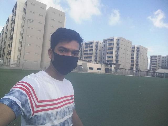 Mann mit Mundschutz vor Wohnblöcken