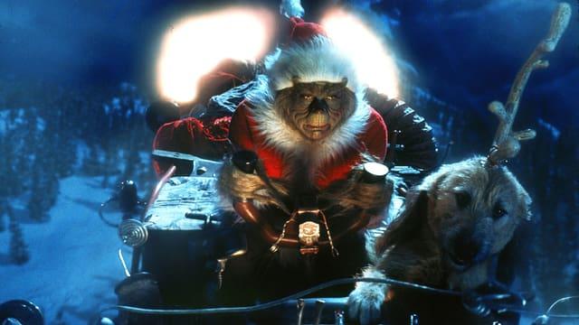 """Szene aus dem Film """"How The Grinch Stole Christmas"""": Ein haariges Monster in Samichlaus-Mütze und -Gewand rast in einem Schlitten über eine schneebedeckte Landschaft. Gezogen wird der Schlitten von einem kleinen Hund, dem ein Rentier-Geweih auf den Kopf gebunden wurde."""