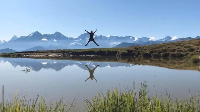 Eine Frau springt in die Luft vor Alpenpanorama. Davor ein See.