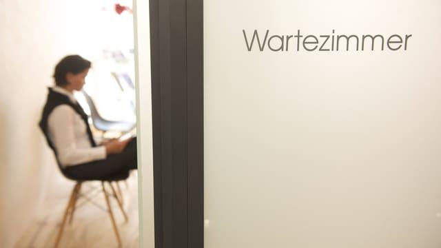 Eine sitzende Frau liest in einem Magazin hinter halb geöffneter Wartezimmertür.