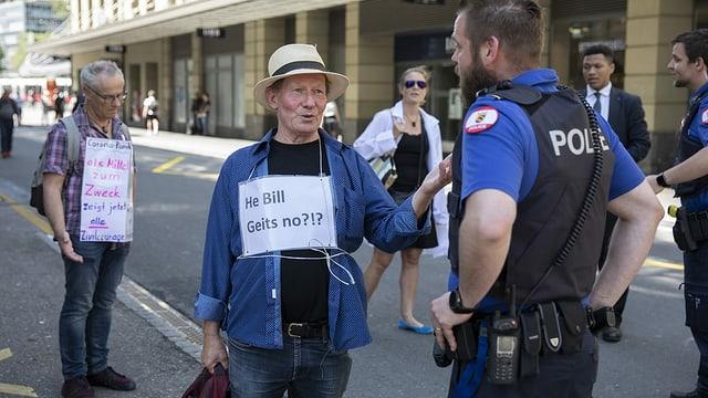 """Demonstranten und ein Polizist stehen auf der Strasse. Ein Mann hat ein Schild umgehängt: """"He Bill, geits no?!?"""""""