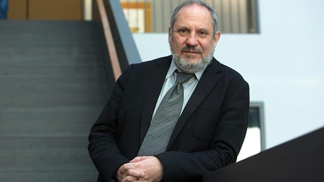 Sigfried Mauer trägt einen Anzug und steht auf einer Treppe.