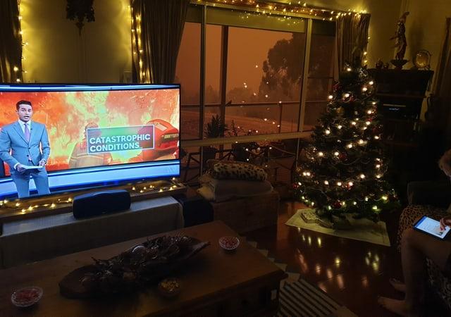 Blick auf einen Fernseher, der über die Brände in Australien berichtet, durch das Fenster ist der Himmel zu erkennen, orange von den Feuern.