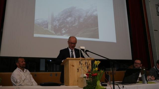 Markus Feltscher il directur da la segirada da bajetgs avant ina fotografia da la tur gigantica da Val