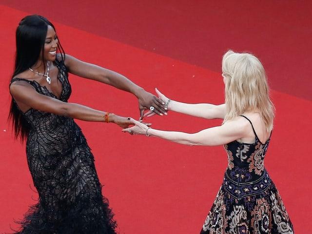 Zwei Frauen laufen aufeinander zu und greifen sich an den Händen.