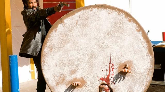Ein Afroamerikaner erschiesst ein Donut-Maskottchen.