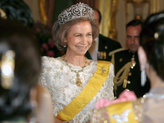 Königin mit Krone und weissem Kleid steht in der Menschenmenge und lächelt.
