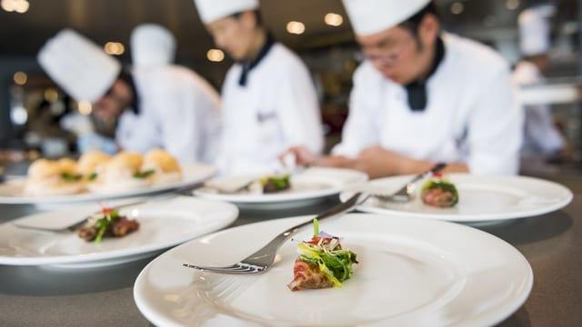 Köche bereiten exklusive Mahlzeit (Häppchen) auf Tellern in der Küche zu