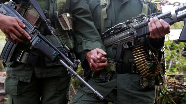Eine Mann und ein Frau, deren Köpfe nicht zu sehen sind, beide schwer bewaffnet, halten sich die Hände.