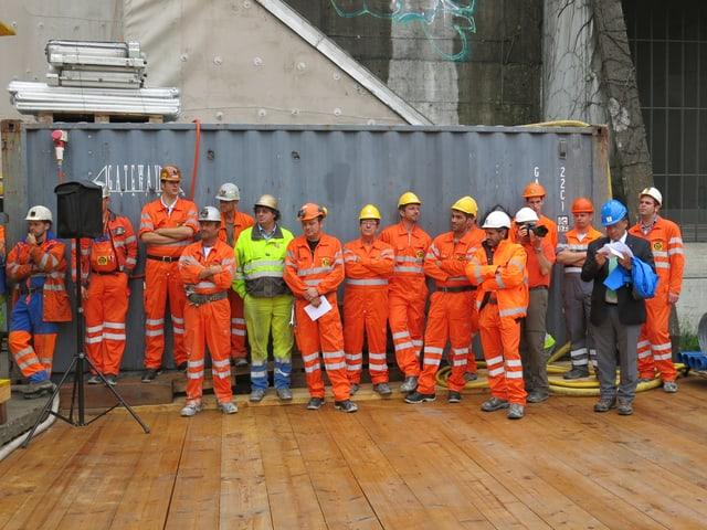 Eine Gruppe von Mineuren in orangen Arbeitskleidern wartet auf die Arbeit.