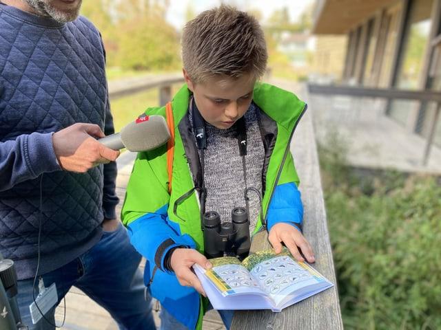 Lorin sucht im Vogelbestimmungsbuch nach einem Vogel