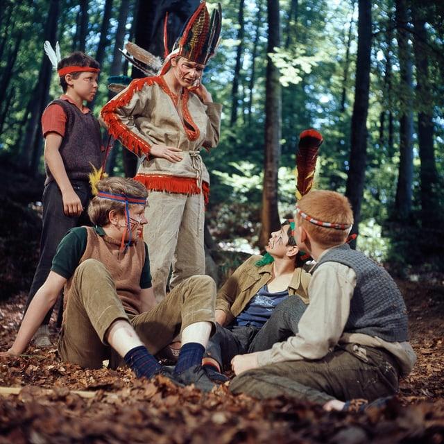 Fünf der Kummerbuben im Wald verkleidet als Indianer. Drei sitzen, zwei stehen.