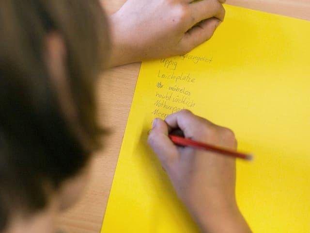 Ein Mädchen schreibt auf ein gelbes Blatt Schulaufgaben.