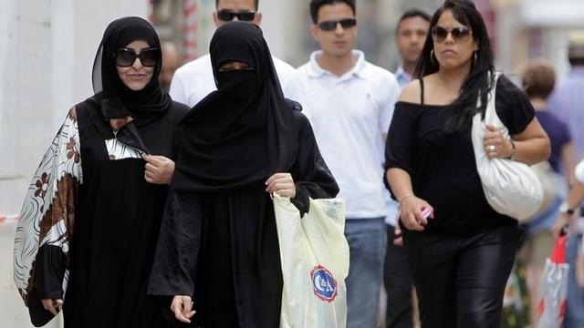 Zwei Frauen laufen auf der Strasse, eine davon mit Einkaufstasche, komplett verschleiert. Hinter ihr eine dritte Frau mit einem Trägerleibchen,