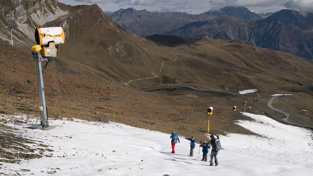 Eine Reihe Schneekanonen am Rand einer künstlichen Piste in Davos. Wanderer.